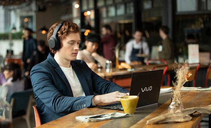 Muž se sluchátky WH-1000XM4 v restauraci
