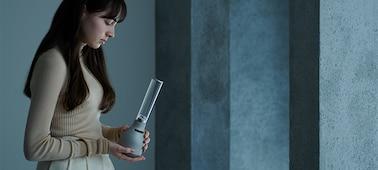 Mladá žena drží skleněný reproduktor Sony LSPX-S3 a demonstruje jeho kompaktní rozměry.