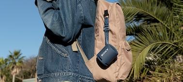 Snímek přenosného bezdrátového reproduktoru XB13 s funkcí EXTRA BASS(TM) připevněného na batohu mladé ženy.