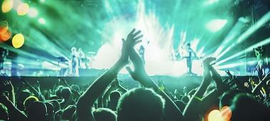 Snímek osob tančících na živém koncertě.