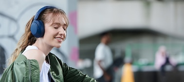 Žena s modrými sluchátky WH-XB910N, zcela pohlcená hudbou