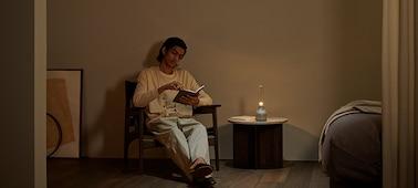 Skleněný reproduktor Sony LSPX-S3 na stole vedle osoby, která si čte při tlumeném osvětlení.