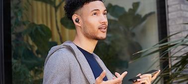 Muž s nasazenými sluchátky WF-1000XM4 telefonující prostřednictvím smartphonu v režimu hands-free