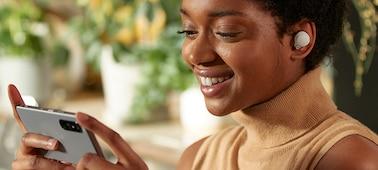 Žena s nasazenými sluchátky WF-1000XM4 sledující obsah na svém smartphonu