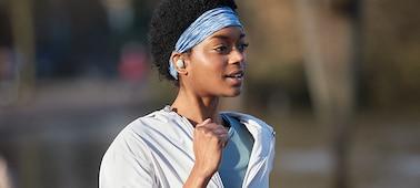 Žena s nasazenými sluchátky WF-1000XM4 běžící v přírodě